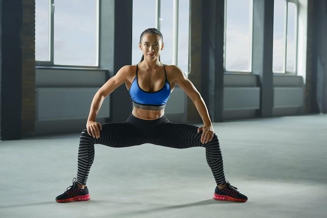 Frontview de mujer atractiva con cuerpo atlético haciendo sentadillas.