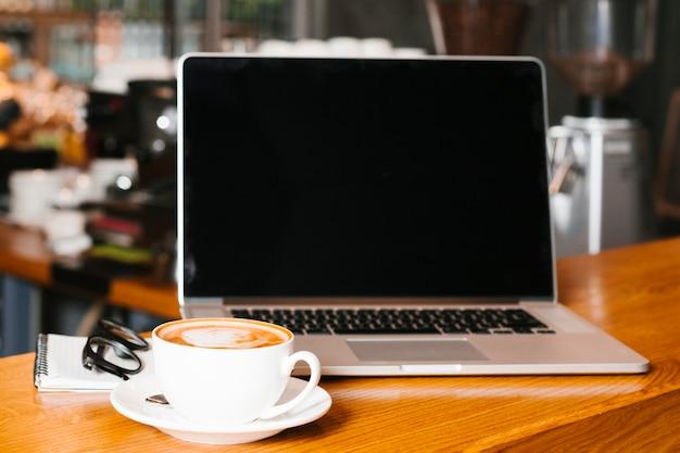 Frontview portátil y café en superficie de madera