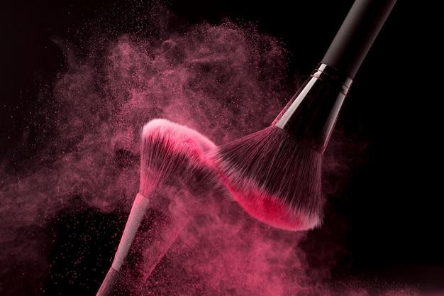 Frotando pinceles de maquillaje grandes con pigmento de color.