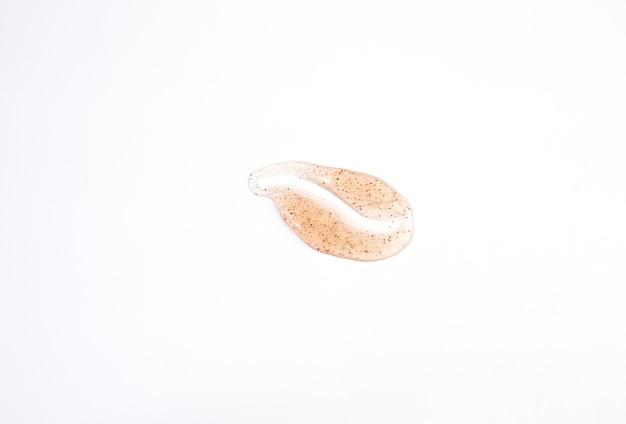 Frotis de exfoliante de azúcar de naranja para el cuerpo y los labios se doblan sobre un fondo blanco. textura de exfoliación corporal cosmética de color naranja.