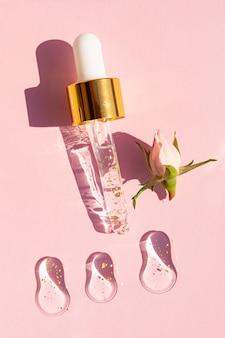 Frotis y gotas con cosméticos para el cuidado de la piel: suero de gel de hialurón de oro de 24k y gotero con líquido. endecha plana de fondo cosmético.
