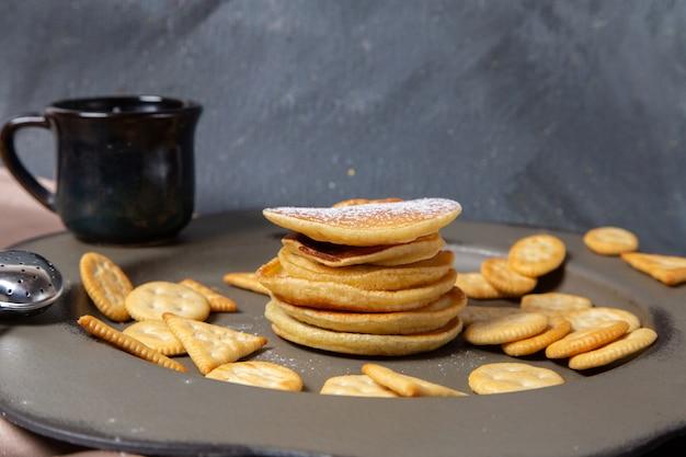 Frotn ver panqueques y galletas con una taza de leche en el fondo gris desayuno comida dulce