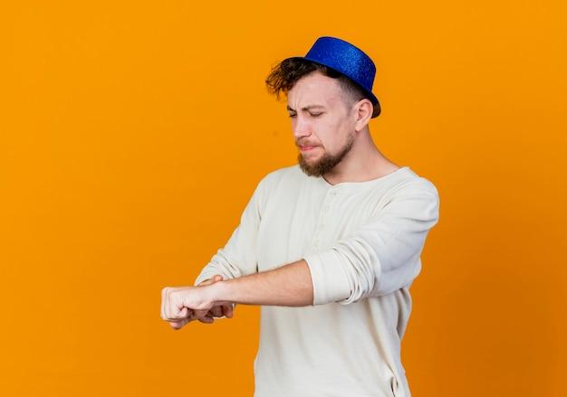 Frunciendo el ceño joven apuesto chico de fiesta eslavo con sombrero de fiesta que señala el dedo en la muñeca finge mirar el reloj aislado sobre fondo naranja con espacio de copia