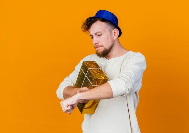 Frunciendo el ceño joven apuesto chico de fiesta eslavo con sombrero de fiesta sosteniendo una caja de regalo tocando la muñeca finge mirar el reloj aislado sobre fondo naranja con espacio de copia
