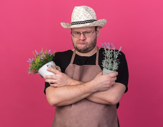 Frunciendo el ceño joven jardinero con sombrero de jardinería sosteniendo y cruzando flores en macetas aisladas en la pared rosa