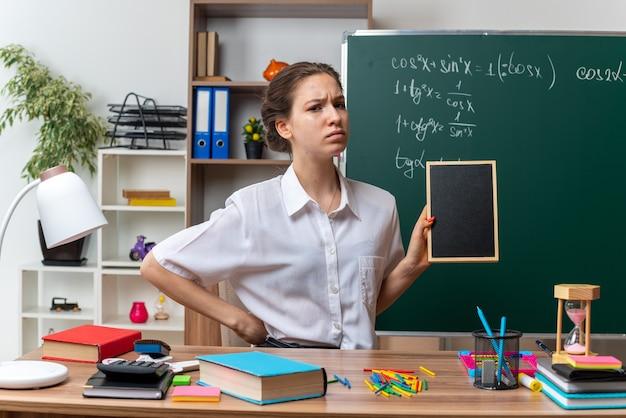 Frunciendo el ceño joven profesora de matemáticas sentada en un escritorio con útiles escolares sosteniendo una mini pizarra manteniendo la mano en la cintura mirando al frente en el aula