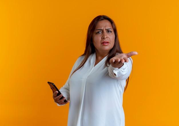 Fruncir el ceño casual mujer de mediana edad caucásica sosteniendo el teléfono y extendiendo la mano