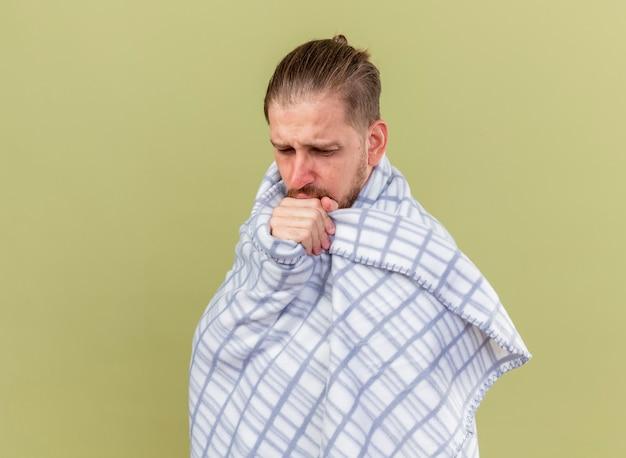 Fruncir el ceño joven apuesto enfermo eslavo de pie en la vista de perfil envuelto en cuadros mirando hacia abajo tosiendo manteniendo la mano en la boca aislada sobre fondo verde oliva con espacio de copia