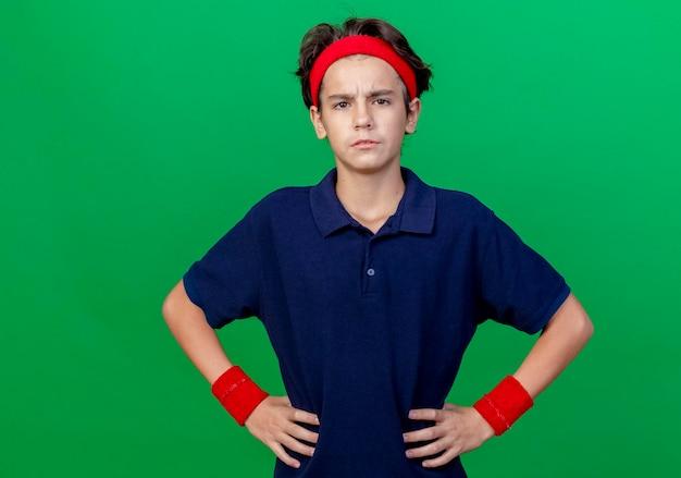 Fruncir el ceño joven apuesto muchacho deportivo con diadema y muñequeras con aparatos dentales manteniendo las manos en la cintura mirando al frente aislado en la pared verde con espacio de copia
