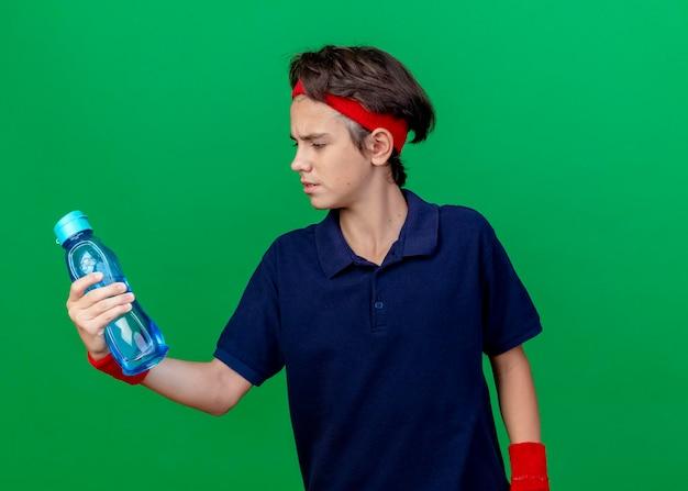 Fruncir el ceño joven apuesto muchacho deportivo con diadema y muñequeras con aparatos dentales sosteniendo y mirando la botella de agua aislada en la pared verde