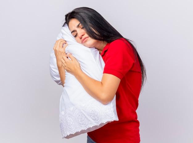Fruncir el ceño a joven caucásica enferma de pie en la vista de perfil de pie en la vista de perfil abrazando la almohada poniendo la cabeza sobre ella con los ojos cerrados aislado sobre fondo blanco con espacio de copia