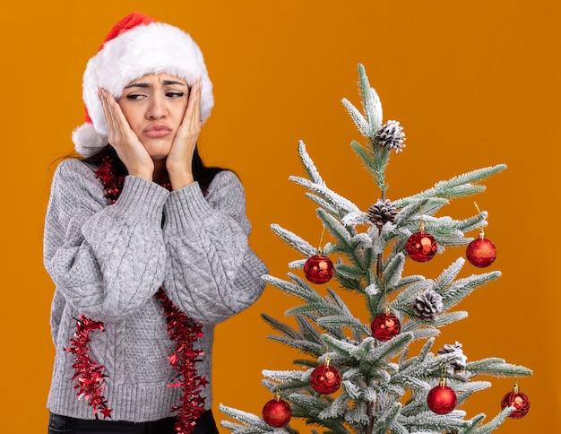 Fruncir el ceño a joven caucásica con sombrero de navidad y guirnalda de oropel alrededor del cuello de pie cerca del árbol de navidad decorado manteniendo las manos en la cara mirando al lado aislado sobre fondo naranja