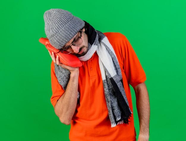 Fruncir el ceño a joven enfermo con gafas, gorro de invierno y bufanda poniendo una bolsa de agua caliente en la cara con los ojos cerrados aislados en la pared verde