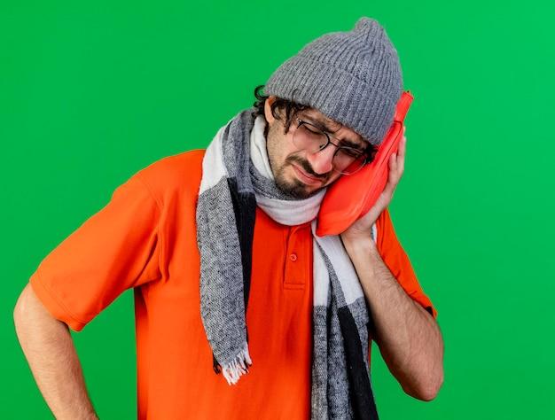 Fruncir el ceño joven enfermo con gafas, gorro de invierno y bufanda sosteniendo una bolsa de agua caliente tocando la cara con los ojos cerrados aislados en la pared verde