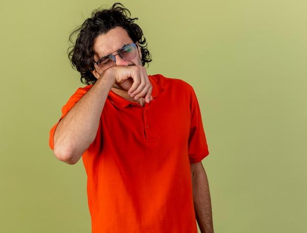 Fruncir el ceño joven enfermo con gafas secándose la nariz con los ojos cerrados aislados en la pared verde oliva