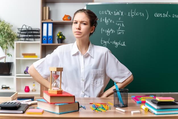 Fruncir el ceño joven profesora de matemáticas sentada en un escritorio con útiles escolares manteniendo las manos en la cintura mirando al frente en el aula