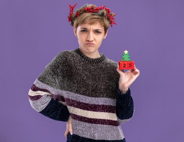 Fruncir el ceño a la niña bonita que lleva corona de cabeza de navidad sosteniendo el juguete del árbol de navidad con fecha mirando a la cámara manteniendo la mano en la cintura aislada sobre fondo púrpura