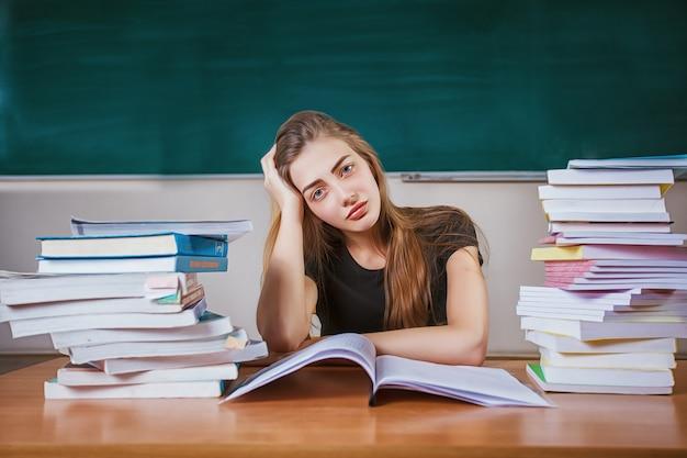 Frustrada estudiante sentada en el escritorio con una enorme pila de libros de estudio en el aula