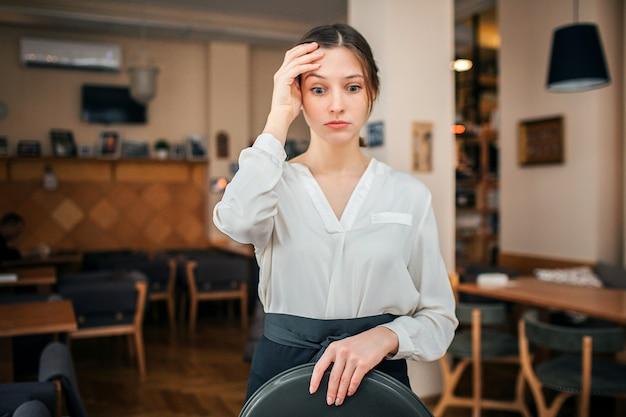 Frustrada joven camarera mira hacia abajo.