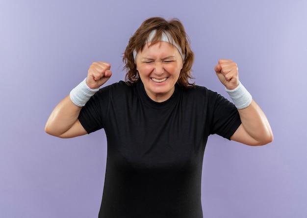 Frustrada mujer deportiva de mediana edad en camiseta negra con diadema apretando los puños con expresión molesta loca loca de pie sobre la pared azul