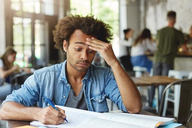 Frustrado y confundido joven estudiante universitario con peinado afro frotándose la frente, esforzándose por comprender un problema matemático complicado mientras hace la tarea en el café, usando un bolígrafo para tomar notas