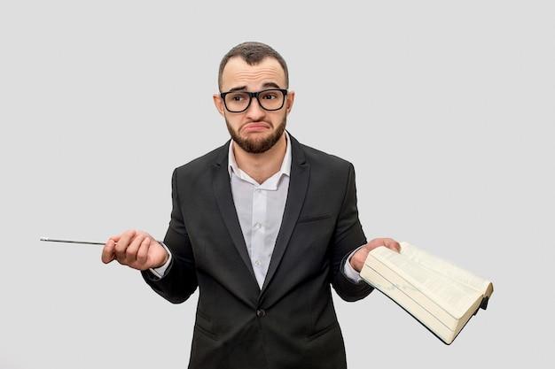 Frustrado e infeliz joven en traje mira directamente a través de lentes. él sostiene la pluma y el libro en las manos.
