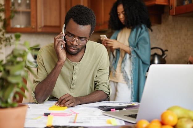 Frustrado joven africano desempleado hablando por teléfono móvil con su amigo, pidiéndole dinero para cubrir los gastos familiares, sin poder pagar más facturas de servicios públicos porque lo despidieron