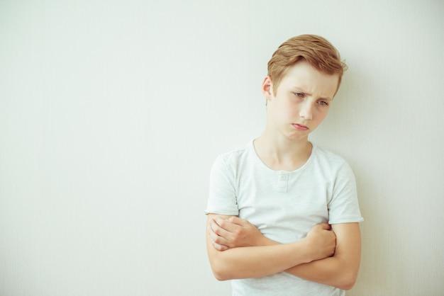 Frustrado muchacho adolescente se encuentra con los brazos cruzados. copia espacio
