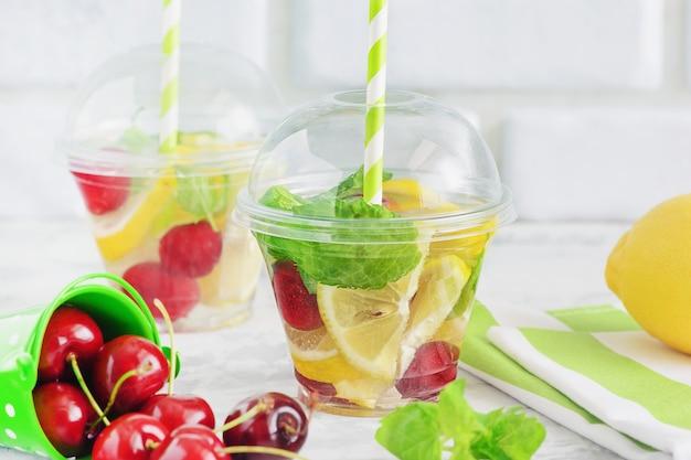 Fruta agua con rodaja de limón, bayas y hojas de menta