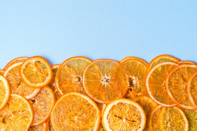 La fruta anaranjada secada salta sobre azul con el copyspace.