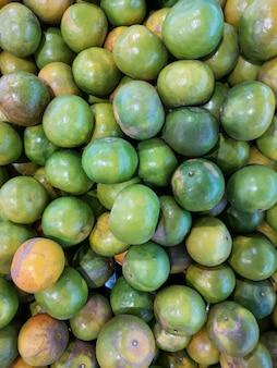 Fruta anaranjada verde fresca para la venta en el mercado. enfoque suave.