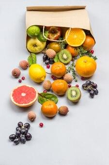 Fruta en bolsa de papel. caqui, kiwi y naranja en mesa.