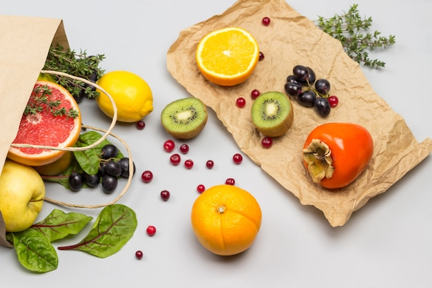Fruta en bolsa de papel. caqui, kiwi y naranja sobre papel. hojas de acelga y arándanos en la mesa.
