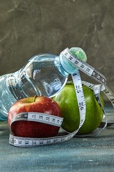 Fruta, una botella de agua, un metro sobre azul.