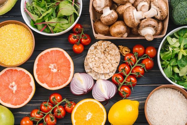 Fruta cítrica; polenta; granos de arroz; vegetales de hoja; pastel de arroz inflado tomates cherry sobre fondo de madera