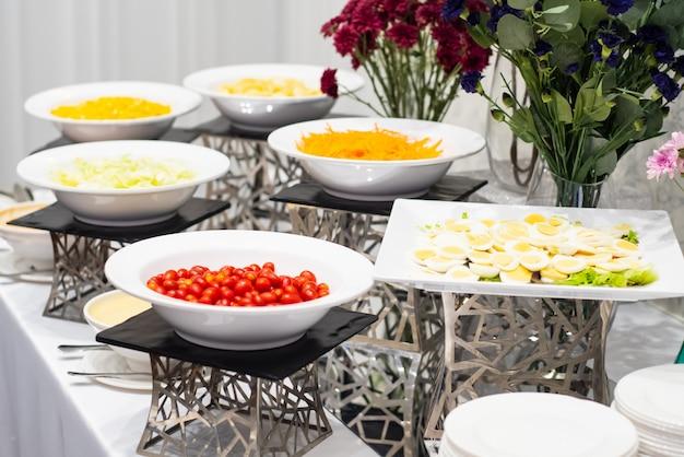 Fruta colorida y pasteles pequeños dispuestos en la esquina del buffet listo para comer