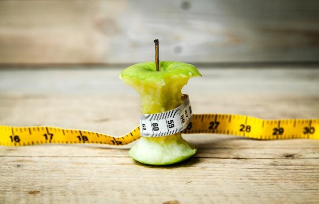 Fruta. corazón de manzana con una cinta métrica alrededor.