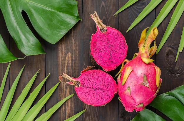 Fruta del dragón en las hojas de palmera y monstruo.
