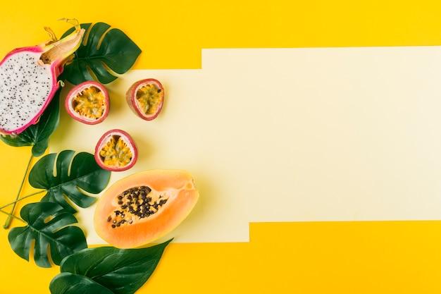 Fruta del dragón a la mitad; maracuyá y papaya con hojas verdes artificiales sobre fondo amarillo.