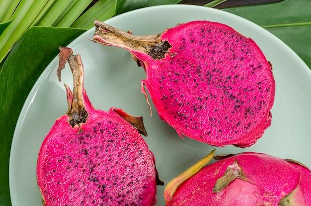 Fruta del dragón en una placa verde. fondo oscuro con hojas de palmera.