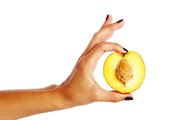 Fruta durazno en mano de mujer