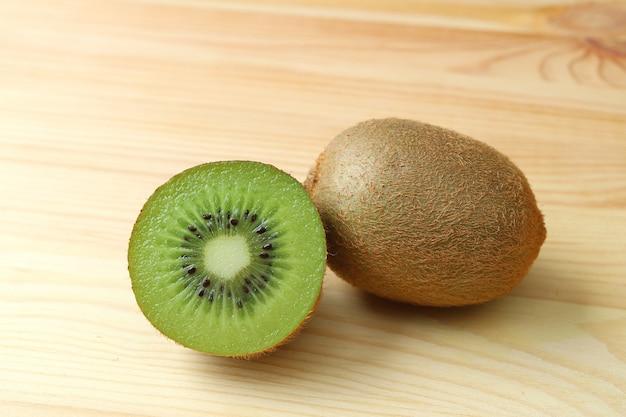 Fruta entera y sección transversal de kiwi maduro verde fresco y jugoso brillante en la mesa de madera