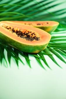 Fruta exótica de papaya sobre hojas de palma verde tropical. diseño de arte pop, concepto creativo de verano. comida vegana cruda.