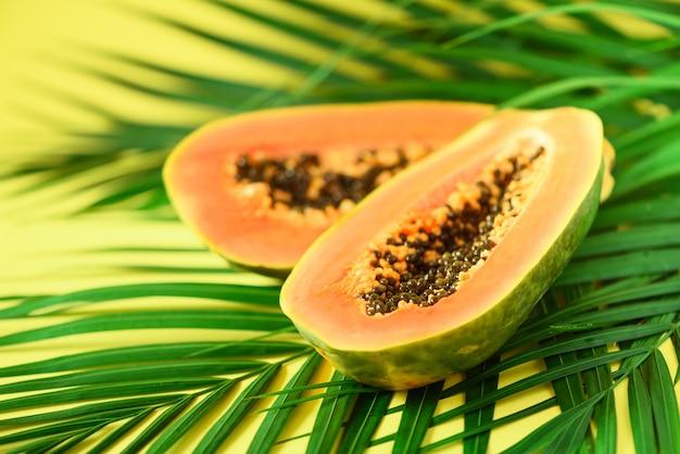 Fruta exótica de la papaya sobre hojas de palma verdes tropicales en fondo amarillo. diseño de arte pop, concepto creativo de verano. comida vegana cruda.