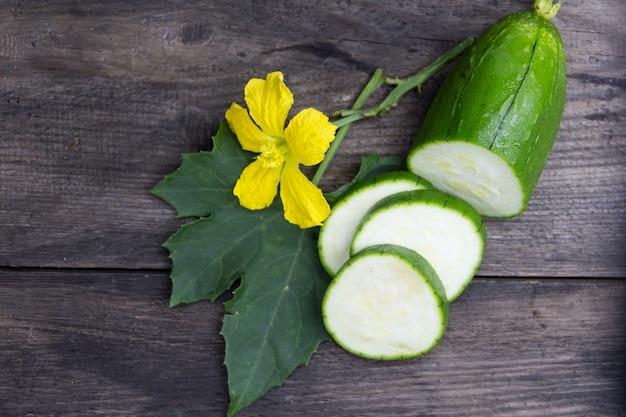 Fruta y flor de la luffa verde sobre fondo de madera rústica