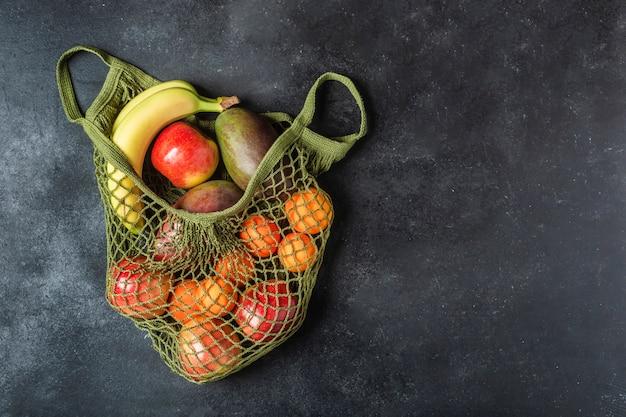 Fruta fresca en una bolsa de hilo verde. plátanos, manzanas, naranjas y mangos.