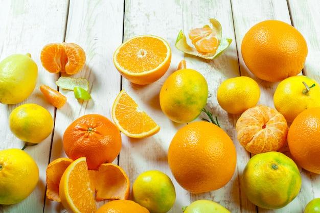 Fruta fresca cítrica sobre la mesa de madera blanca.