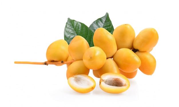 Fruta fresca de palmera datilera en superficie blanca