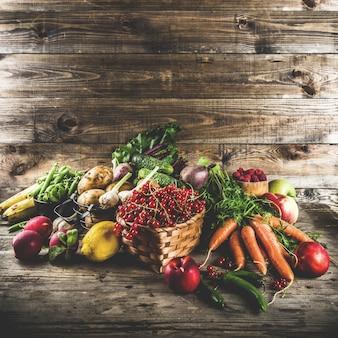 Fruta fresca de verano, bayas y verduras sobre fondo rústico de madera