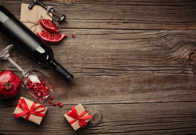 Fruta de granada madura con una copa de vino, una botella y un regalo en un fondo de madera